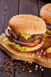 Os hamburgueres saborosos da carne fresca com salada e queijo serviram na placa de madeira imagens de stock