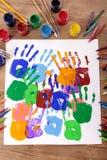Os handprints das crianças e o equipamento da arte, a arte e o ofício classificam, mesa da escola, sala de aula Foto de Stock Royalty Free