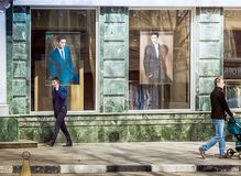 Os homens andam abaixo da rua perto da loja de roupa dos homens em Saratov fotos de stock royalty free