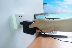 Os homens as mãos do ` s que são obstruem dentro o carregador do cabo de alimentação do adaptador do laptop no assoalho de madeir imagens de stock