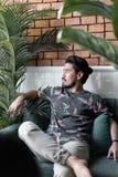 Os homens asi?ticos vestem a camisa tropical com os olhares pretos da barba e do noivo que sentam-se no sof? na cena artificial d fotos de stock