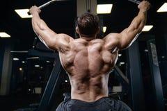 Os homens atléticos do halterofilista forte brutal que bombeiam acima muscles com d fotografia de stock