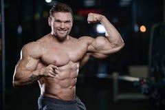 Os homens atléticos do halterofilista forte brutal que bombeiam acima muscles com d imagem de stock royalty free