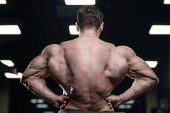 Os homens atléticos do halterofilista forte brutal que bombeiam acima muscles com d fotos de stock