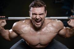 Os homens atléticos do halterofilista forte brutal que bombeiam acima muscles com d fotografia de stock royalty free