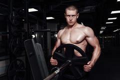 Os homens atléticos fortes musculares que bombeiam acima muscles e que treinam no gym Indivíduo considerável do halterofilista qu imagem de stock royalty free