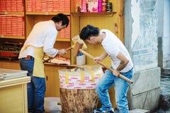 Os homens chineses com malhos de madeira estão esmagando porcas, Lijiang Foto de Stock