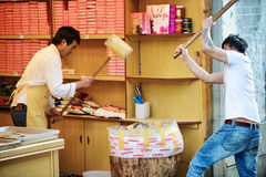 Os homens chineses com malhos de madeira estão esmagando porcas para fazer doces Imagem de Stock