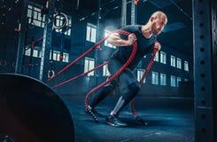 Os homens com corda da batalha lutam cordas exercitam no gym da aptidão Crossfit foto de stock royalty free