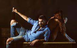 Os homens com mulher sensual bebem o álcool e apreciam o momento Relaxando e apreciando o conceito Pares românticos que sentam-se foto de stock