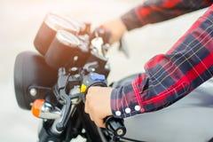 Os homens da mão de Closup vestem uma camisa de manta vermelha, conduzem uma motocicleta do vintage Imagens de Stock Royalty Free