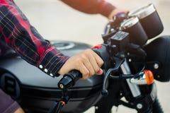 Os homens da mão de Closup vestem uma camisa de manta vermelha, conduzem uma motocicleta do vintage Fotos de Stock Royalty Free