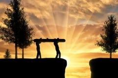 Os homens da silhueta dois levam um log para pavimentar a maneira através do abismo imagem de stock royalty free