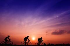 Os homens da silhueta três montam bicicletas no por do sol com fundo alaranjado-azul do céu Fotografia de Stock Royalty Free
