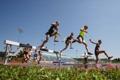 Os homens da trilha da corrida de obstáculos saltam a água Imagem de Stock