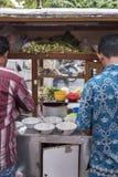 Os homens de Indonésia preparam o alimento em um carro de madeira do impulso do alimento da rua do vintage em Jakarta, Indonésia imagem de stock royalty free