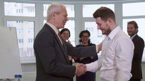 Os homens de negócios agitam as mãos no escritório filme