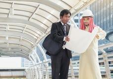 Os homens de negócios asiáticos e os arquitetos árabes consultaram no projeto comum fotos de stock