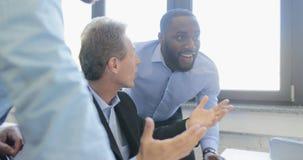 Os homens de negócios de sorriso felizes agrupam a discussão do ponto no tela de computador, executivos da equipe que fala sobre  vídeos de arquivo