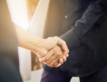Os homens de negócios estão agitando as mãos após negociações bem sucedidas no negócio, o conceito do avanço do negócio com a col foto de stock