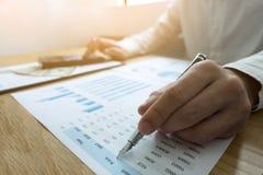 Os homens de negócios estão apontando números, gráfico, carta em resultados de negócio Conceito do negócio foto de stock