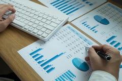 Os homens de negócios estão apontando números, gráfico, carta no resul do negócio fotos de stock royalty free