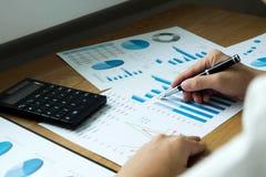 Os homens de negócios estão apontando números, gráfico, carta no resul do negócio imagem de stock royalty free