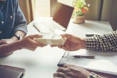 Os homens de negócios estão pagando a compensação No escritório foto de stock