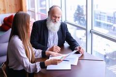 Os homens de negócios experientes aposentaram-se sorrisos e compartilham do conselho com o ne foto de stock