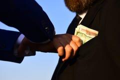 Os homens de negócios fazem o negócio A mão masculina põe o dinheiro no bolso do terno Foto de Stock Royalty Free