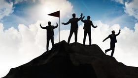 Os homens de negócios na realização e no conceito dos trabalhos de equipe imagens de stock