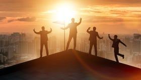 Os homens de negócios na realização e no conceito dos trabalhos de equipe fotos de stock