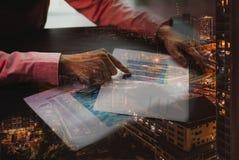 Os homens de negócios no vestido da cor clara são apontar do papel com estatísticas com Metropole e tráfego no fundo fotos de stock royalty free