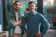 Os homens de negócios profissionais alegres estão levantando no escritório com sorriso imagem de stock