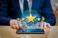 Os homens de negócios que apontam cinco estrelas da estrela para impulsionar avaliações incorporadas telefonam ao suporte fotos de stock royalty free