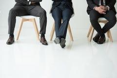 Os homens de negócios que sentam-se nas cadeiras isoladas no branco, homens de negócios agrupam o conceito Fotografia de Stock