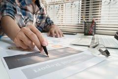 Os homens de negócios que trabalham com dados do gráfico no escritório, gerentes da finança encarregam-se, negócios do conceito e fotografia de stock