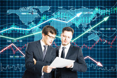 Os homens de negócios examinam no papel o fundo dos gráficos de negócio Fotografia de Stock