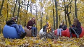 Os homens de pele escura e brancos, três mulheres sentam-se pelo fogo na floresta do outono em pufes e bebem-se da garrafa térmic filme