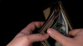 Os homens distribuem dólares do dinheiro da bolsa Dólar e Hryvnia Fundo preto vídeos de arquivo