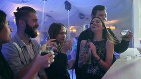Os homens e as jovens mulheres com cocktail coloridos fazem um brinde e têm o bom tempo perto do contador da barra no clube notur filme
