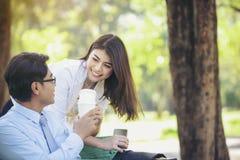 Os homens e as mulheres asiáticos de negócio estão relaxando com café no peixe-agulha imagem de stock royalty free