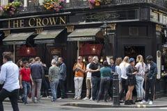 Os homens e as mulheres bebem a cerveja e o fumo fora do bar da coroa perto do quadrado de Leicester em um dia ensolarado Imagem de Stock