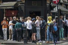 Os homens e as mulheres bebem a cerveja e o fumo fora do bar da coroa perto do quadrado de Leicester em um dia ensolarado Fotos de Stock