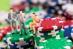 Os homens e as mulheres do brinquedo são estando e de assento em microplaquetas de pôquer Imagem de Stock Royalty Free
