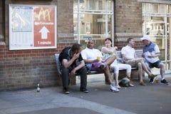 Os homens e as mulheres estão sentando-se em um banco fora da estação, falando animatedly Fotografia de Stock