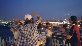 Os homens e as mulheres felizes estão dançando com mãos levantadas no partido exterior no telhado quando o DJ misturar a música c filme
