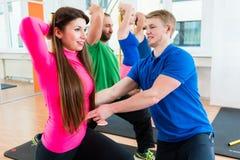 Os homens e as mulheres no gym que faz pilates malham fotografia de stock royalty free