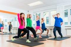 Os homens e as mulheres no gym que faz pilates malham foto de stock royalty free