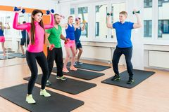 Os homens e as mulheres no gym que faz pilates malham fotos de stock
